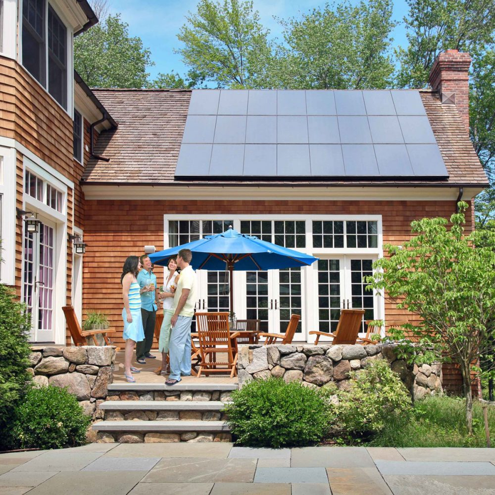 People on a patio outside a house with solar panels